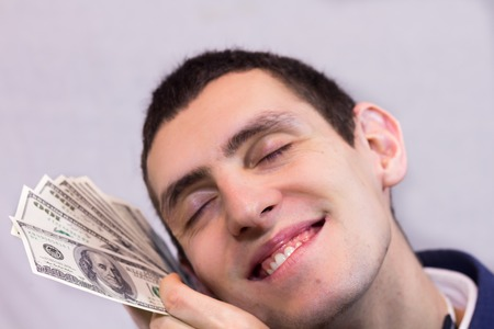 rejoices: Happy man holding a lot of dollars and rejoices