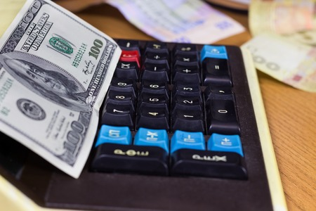vintage background: Man makes calculations on a retro calculator with money on it Stock Photo