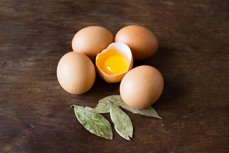 farm fresh: Broken chicken egg and bay leaf on wooden background Stock Photo