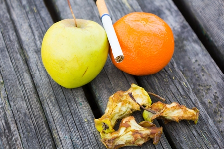 rancid: Fresh fruits orange and apple near putrid and cigarette healthy lifestyle against unhealthy