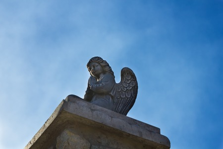 praying angel: Beautiful statue of a praying angel on a background of blue sky Stock Photo