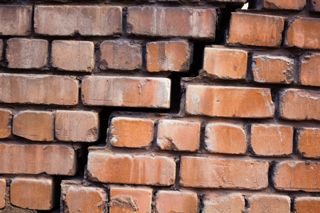 Large and wide crack in the wall of red brick Foto de archivo