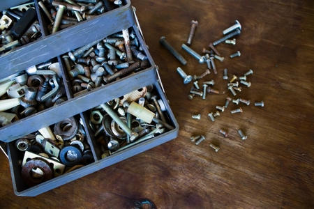 bolts and nuts: A lot of small details screws bolts nuts in a special box for tools on a wooden background