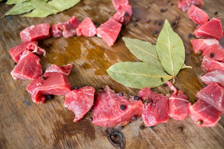 bacon love: Pieces of meat as heart lies a bay leaf and black pepper on an original wooden background