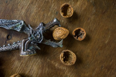 antiquary: Vintage Original Nutcracker in the form of a dragon chop walnuts next to the peel on a wooden background