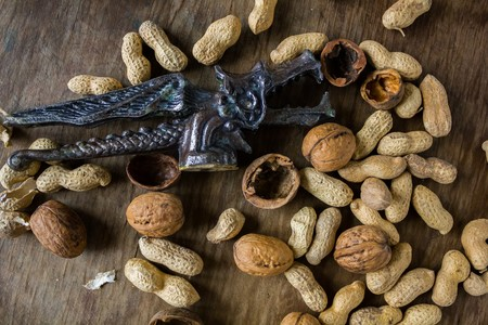 cobnut: Walnuts and peanuts in a peel and vintage Dracon Nutcracker on a wooden table