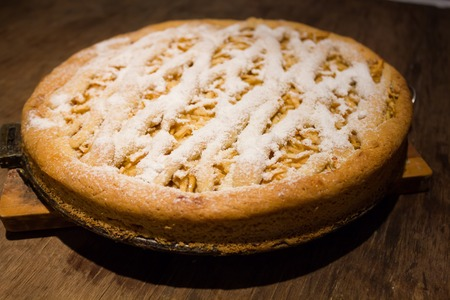 home baked: Tasty home baked apple pie with icing sugar on wooden background