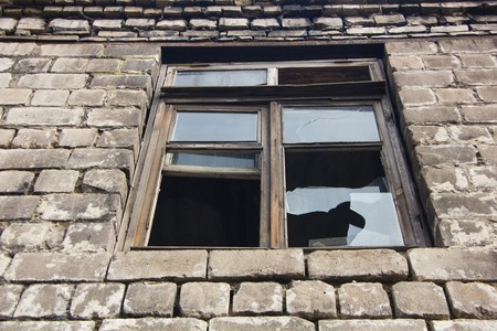 crazed: Broken window in an old brick building