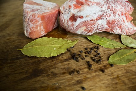 frozen meat: Frozen meat on a wooden table with spices with black pepper and bay leaf