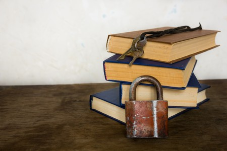 bibliomania: A stack of old big books and vintage lock and key near