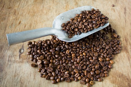 gusto: Coffee beans and shovel on wooden background