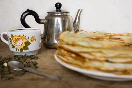 rubicund: Stack of pancakes vintage teapot cup with floral print green tea leaves and a teaspoon