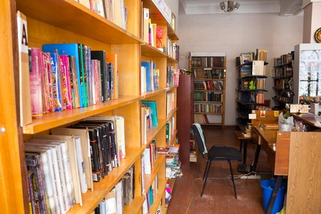 librarians: View of the plurality of shelves with books in the library and the librarians desk