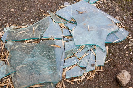 Broken shards of glass lying on the ground Stock Photo