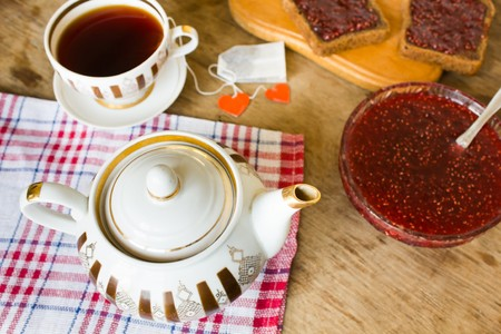 choke: light breakfast or lunch , Raspberry jam slices of black bread Vintage cup of tea and teapot