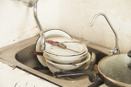 appalling: A lot of dirty dishes in the old poorly furnished kitchen Stock Photo