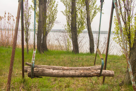 space weather tire: Original makeshift swing on the lake in spring Stock Photo