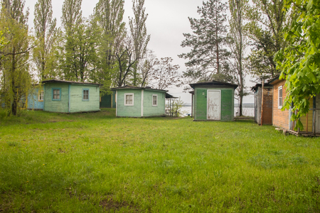 Small tourist wooden green houses on the lake in early spring Banco de Imagens