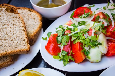 Delicious fresh salad with tomato sauce sliced bread and cut lemon on a stylish black table