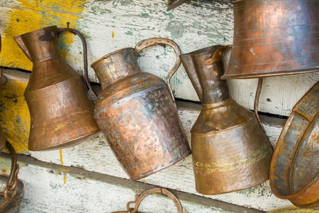 Large old antique copper cans hanging on the wall Foto de archivo
