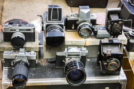 Many different old vintage cameras at a flea market