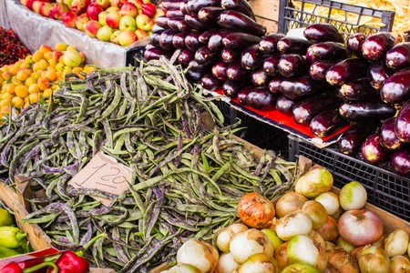 Eggplant onions beans and other fruits and vegetables on a market stall