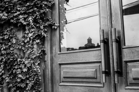 Black and white photo beautiful stylish wooden door next to ivy and a reflection of the Cathedral of Tbilisi, Georgia Foto de archivo