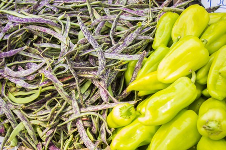 Lots of ripe beans and sweet pepper on the counter of the vegetable market Foto de archivo