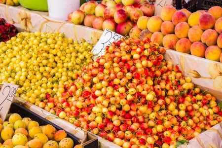 Big juicy ripe delicious sweet cherries next to other fruits are sold at the counter Foto de archivo