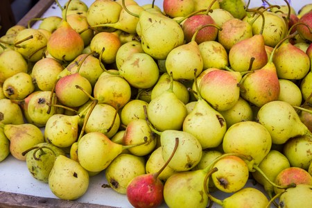 A lot of ripe juicy pears on the counter of the vegetable market Foto de archivo