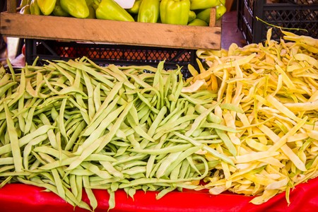 greenbeans: Lots of ripe beans and sweet pepper on the counter of the vegetable market Stock Photo