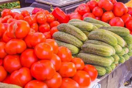 Juicy and ripe cucumbers and tomatoes are on the counter market