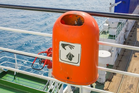 dumpster: Red plastic rubbish bin with a sign hand throw garbage on the ship against the blue sea