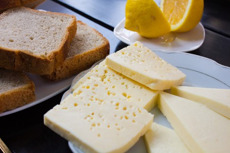 various pieces of cheese lying on a plate next to the lemon and slices of brown bread on a white plate and a stylish black table.
