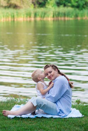 f�minit�: Femme enceinte et son fils de 2 ans sur l'herbe verte. Concept de la maternit� et de la f�minit�