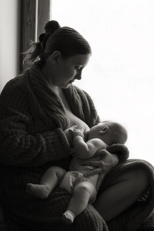 adult breastfeeding: Woman breastfeeding near a window, black and white