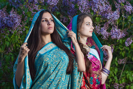 Asian women with mehndi in lilac bushes