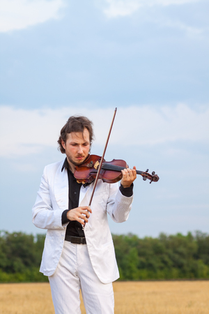 violinist: Violinist playing the violin in the field