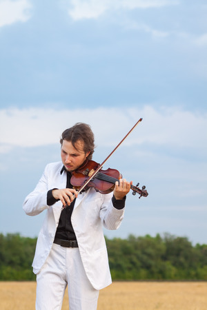 violinista: Violinist playing the violin in the field