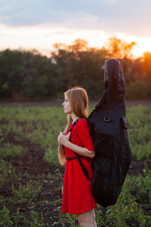 Woman musician travelling with cello outdoors