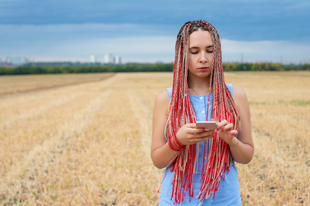 Caucasian woman with african pigtails using smartphone outdoors