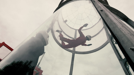 Girl paratrooper performing a parachute jumping in a wind tunnel