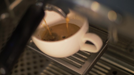 Close up strong coffee pouring in white cup from coffee machine in cafeteria