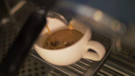 Coffee pouring into cup from coffee machine in restaurant close up Stock Photo
