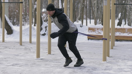 Athlete man doing crossfit exercise with expander on outdoor winter training Stock Photo