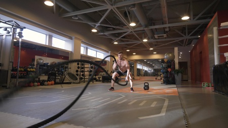 Muscular man training workout exercise with ropes in fitness club