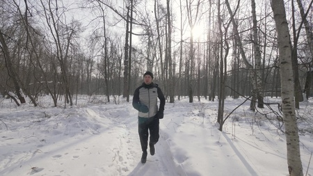 Portrait athlete man running in winter forest close up. Winter jogging in city park