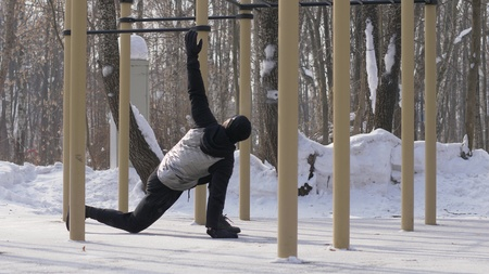 Fitness man doing squat exercise on winter sports ground outdoor