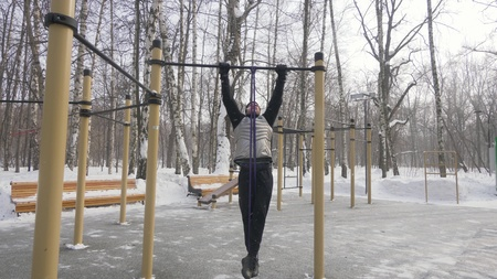 Bearded man doing pull up exercise during outdoor training on sport ground Stock Photo