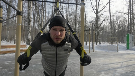 Man bodybuilder doing squat exercise on sports ground in winter park Stock Photo